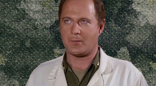 David Ogden Stiers in his army uniform and lab coat against a camoflauge background from MASH