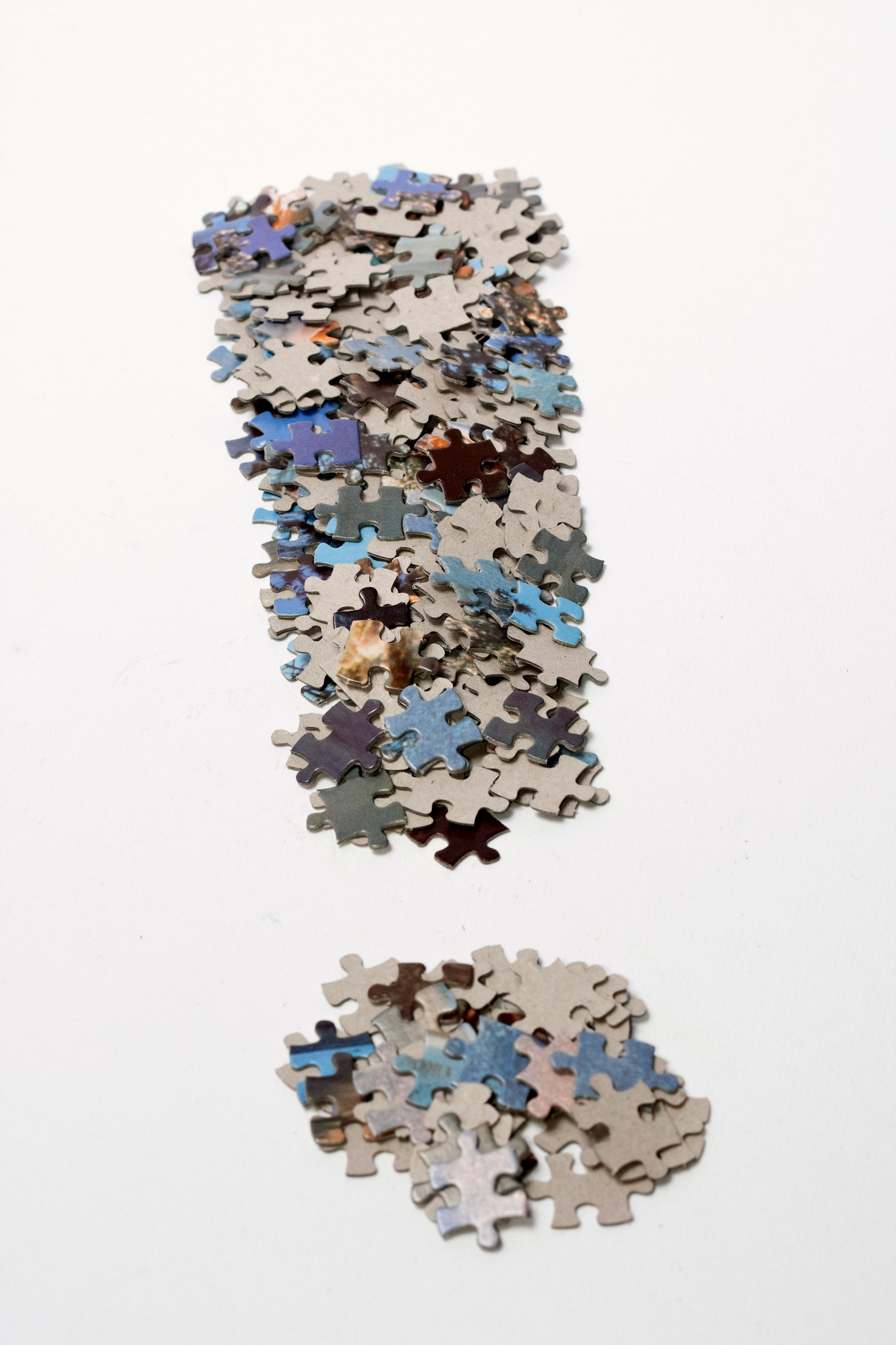A fat exclamation mark consisting of blue and violet jigsaw puzzle pieces with a gray carboard back on a white background.