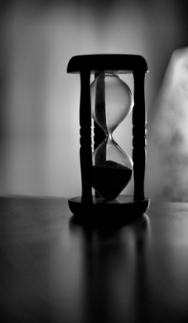 A wooden hour glass with the sand in the bottom section in focus in a grayscale photo